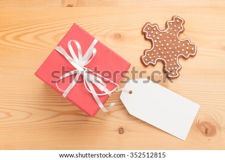 Red gift box with blank white tag and Christmas cookie on wooden background. Above view