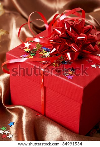 Red gift box with bows and stars on golden silk background - stock photo