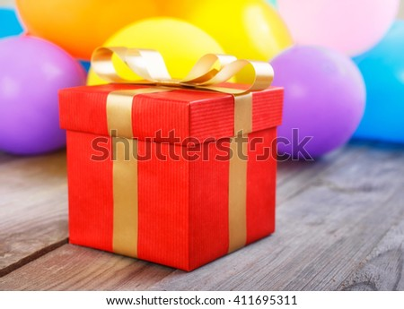 Red gift box with gold ribbon on the wooden table close up against the backdrop balloons - stock photo