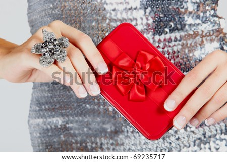 red gift box with satin bow in hands of a young woman wearing a large flower ring and a silver sequin dress .