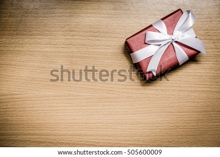 Red gift box with white ribbon bow on wooden background. Present for birthday.