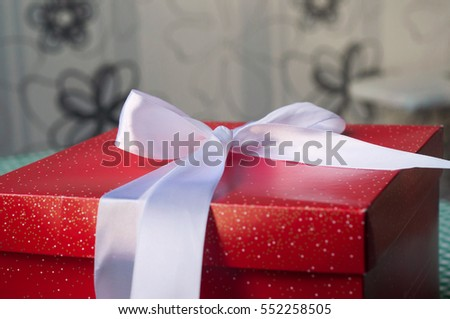 Red gift box with white ribbon on the table