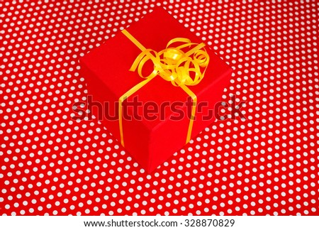 Red gift box with yellow ribbon isolated on red background with white dots - stock photo