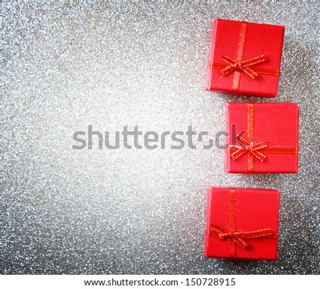 red gift boxes on glittersilver background - stock photo