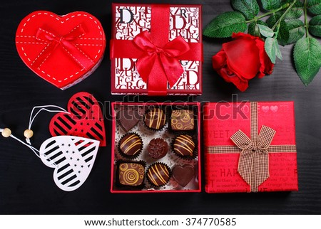 red gift boxes with chocolate pralines and rose on black background for valentine`s day  - stock photo