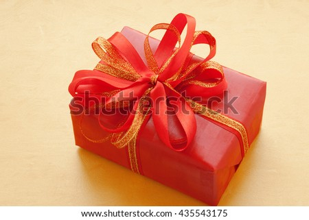 Red gift on a golden background. Greeting card. Oriental style. Chinese present.