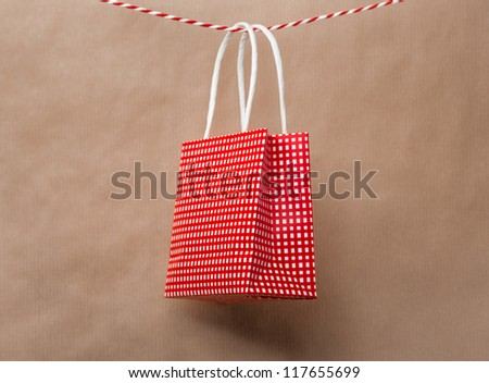 Red gift package paper bag hanging on a ribbon. Old brown paper background - stock photo