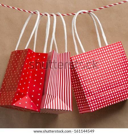 Red gift package paper bags hanging on a ribbon. Old brown paper background - stock photo