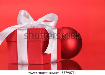 Red gift tied with a white satin ribbon bow.