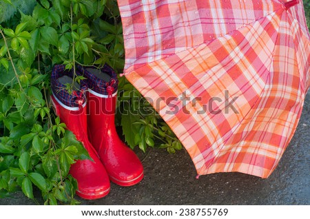 Red girlish gumboots and open umbrella drying in garden - stock photo