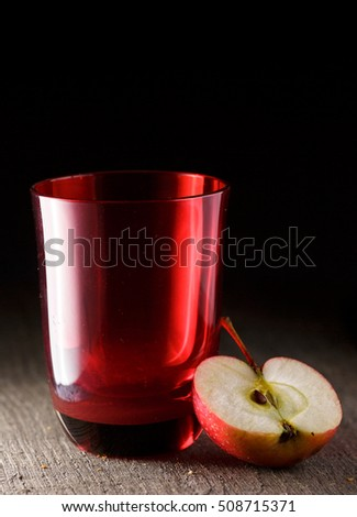 red glass and red apple. cut apple