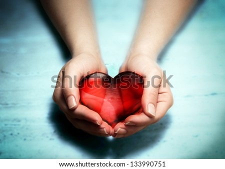Red glass heart in woman hands - stock photo
