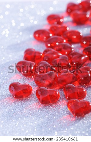 Red glass-hearts on silver sparkle background - stock photo