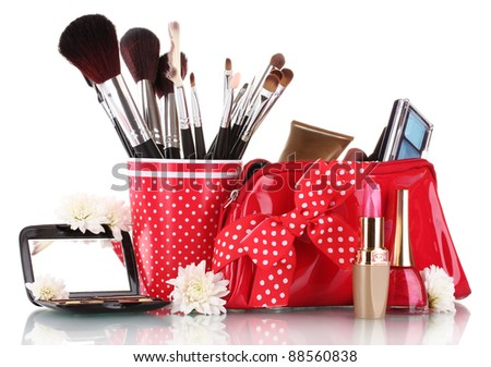 red glass with brushes and makeup bag with cosmetics isolated on white - stock photo