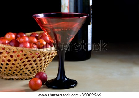 red glass with drink and cherry-plum