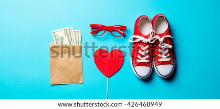 red glasses, gumshoes, money and heart shaped toy on the blue background - stock photo