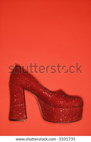 Red glitter high heel shoe against red background. - stock photo