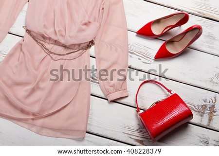 Red glossy bag and dress. Bright red purse on table. Young lady's luxury handbag. Glossy leather accessory on sale. - stock photo