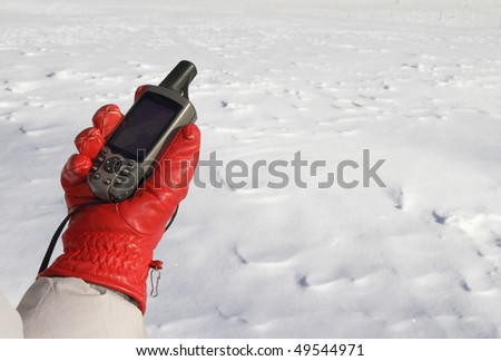 red glove with a GPS navigator on a background of white snow