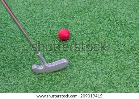 Red golf ball on golf course with mini golf stick  - stock photo