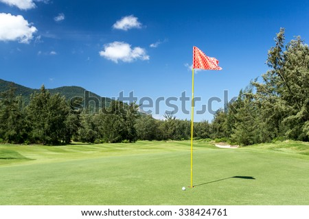 red Golf flag in hole and ball with blue sky - stock photo