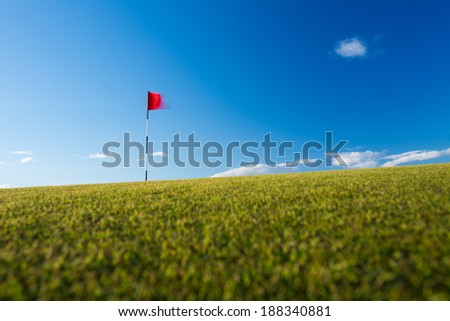 Red golf flag on a golf course, moving in the wind (motion blurred image); St. Andrews, Scotland - stock photo