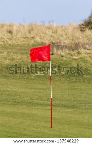 Red golf flag on a seaside links course in the UK - stock photo
