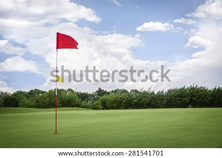 Red golf flag on green fairway with beautiful blue sky, with empty copyspace.