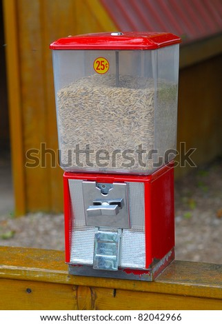 Red Grain dispenser for hand feeding petting zoo animals - stock photo