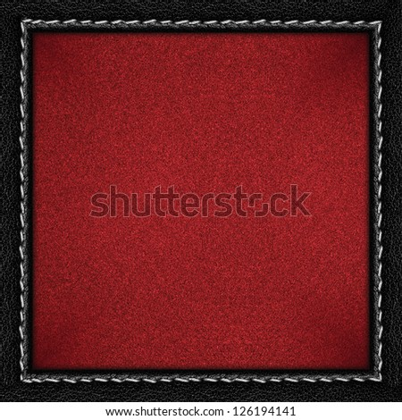 red grainy paper background in black leathery frame with seam
