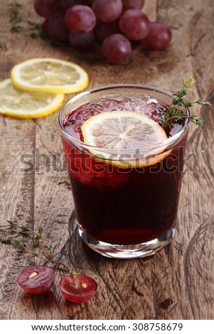 red grape beverage in glass on wooden background
