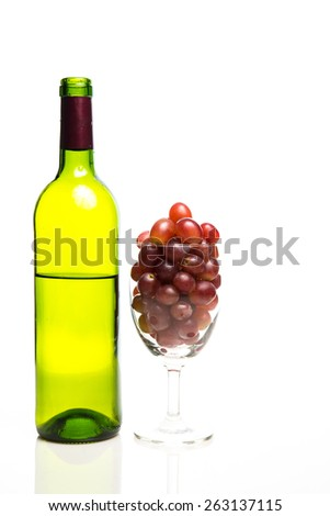 red grape in wine glass with wine bottle isolated on white. - stock photo