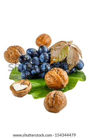 Red grape with walnuts on a green leave isolated on white background  - stock photo