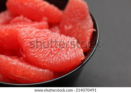 Red Grapefruit slices in a black bowl on black background. Closeup. - stock photo