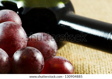 Red grapes and a bottle of red wine - stock photo
