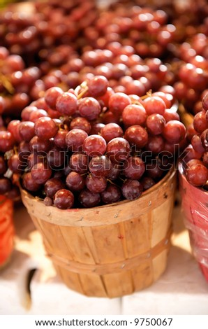 red Grapes for sale in a basket on a open air market stall - stock photo