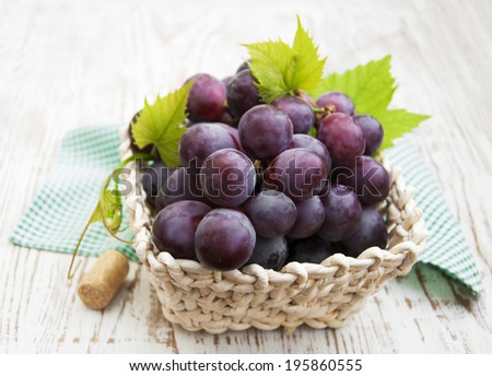 red   grapes served in basket on a wooden background - stock photo