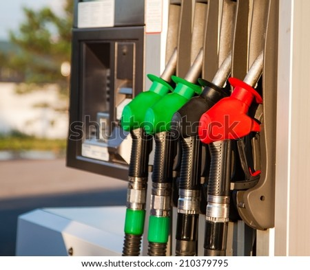 Red, green and black fuel pumps at petrol station - stock photo