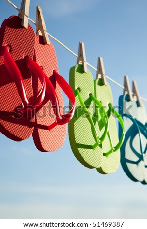 Red, green and blue flip-flops hanging on a line with a sky background - stock photo
