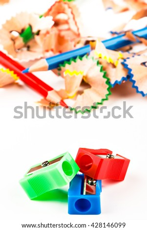 Red, green and blue pencil sharpener with color shavings pencils. Vertical image.