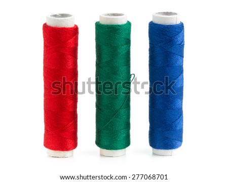 Red, green and blue sewing yarn rolls on white background close up view - stock photo