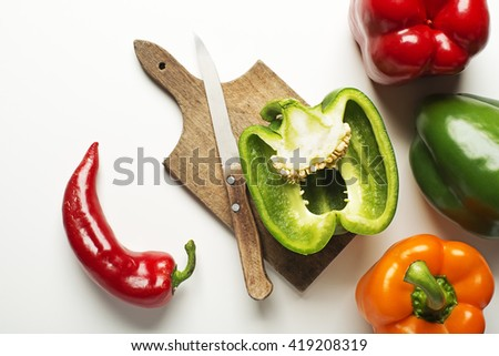 Red, green and orange bell peppers on white background.