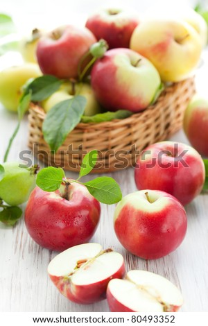 Red,green and yellow apples with leaves in the basket - stock photo
