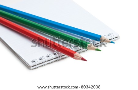 red  green blue pencils and notebook isolated on a white  background - stock photo