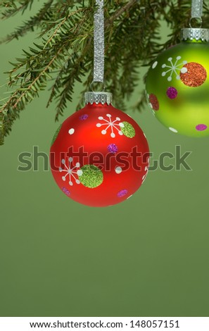 Red & green Christmas balls hanging from Christmas tree on green background. Shallow DOF. - stock photo