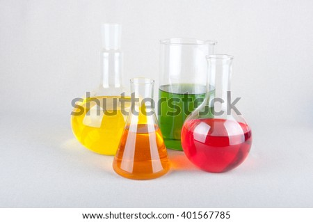 Red, green, orange and yellow liquid inside laboratory bulbs on white background