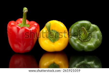 Red,green,yellow wet bell peppers isolated on black background with water drops