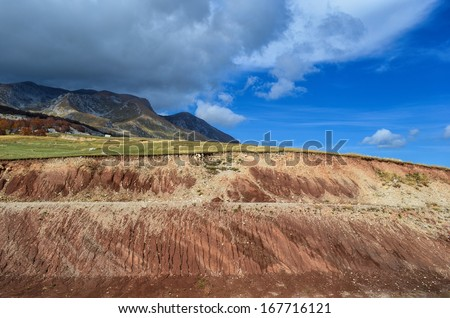 Red ground cross-section in foreground, partly cloudy sky and high mountains in the distance - stock photo