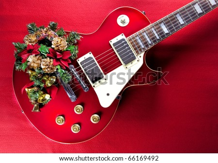 Red guitar with christmas ornaments. Image for christmas / holiday season music event. - stock photo