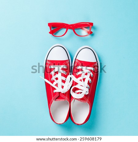 Red gumshoes with white shoelaces and glasses on blue background. - stock photo